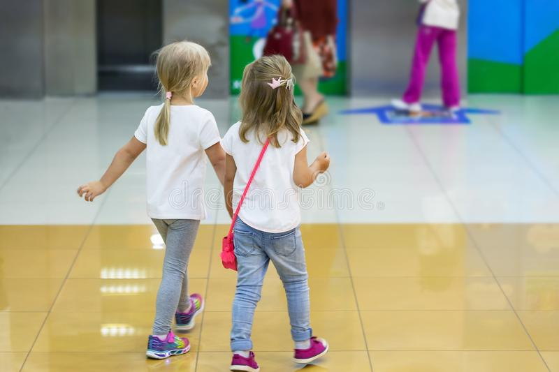 Two cute blond little girls walking together in mall. Pair of kid friends holding hands during walk. Toddler friendship royalty free stock photo