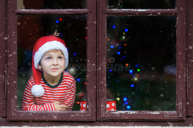 Two cute boys, brothers, looking through a window, waiting for S royalty free stock photos