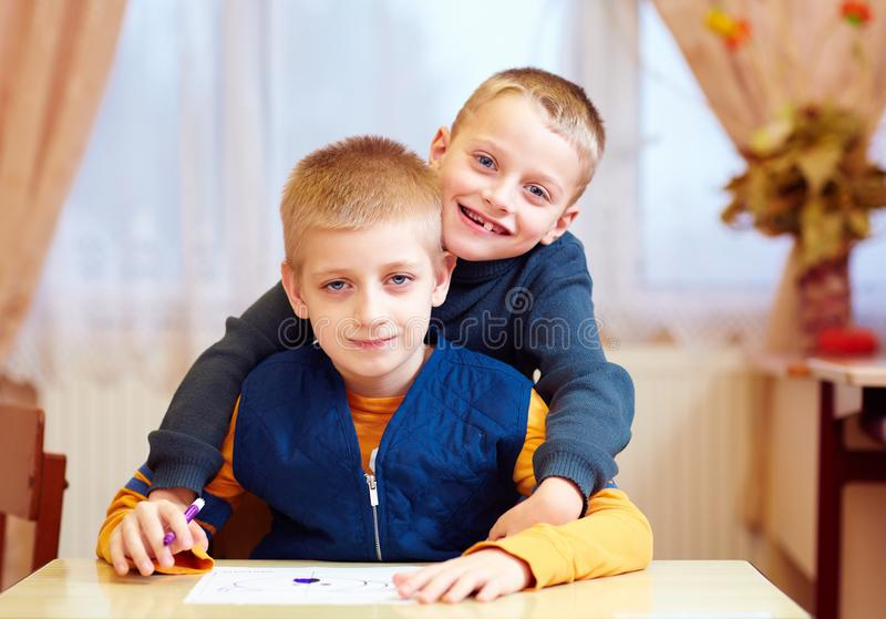 Two cute kids, friends in rehabilitation school for kids with special needs royalty free stock image