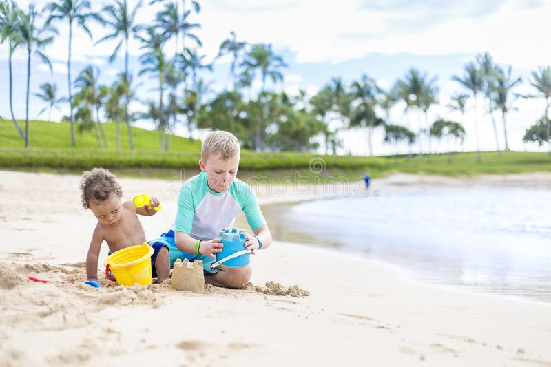 Two cute boys playing in the sand together on a tropical beach vacation stock photo