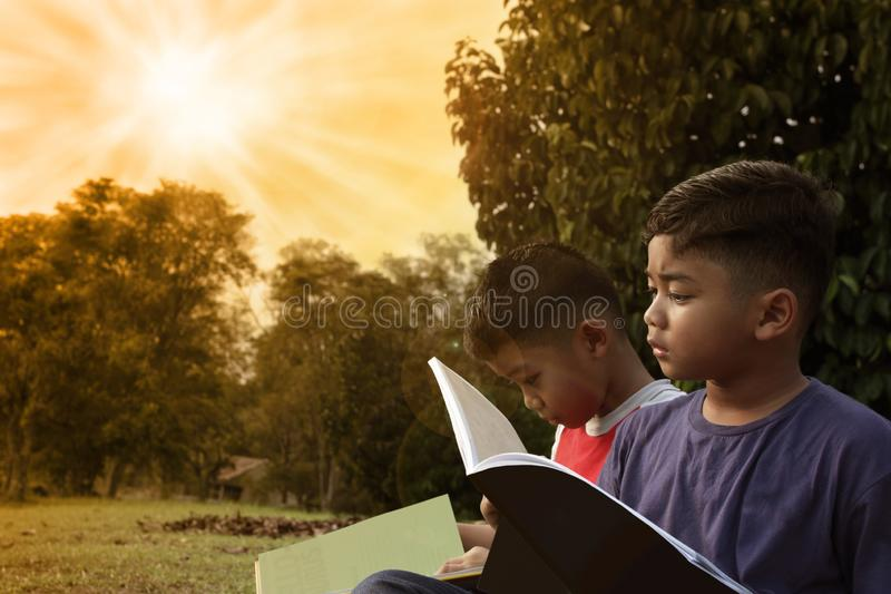 Two cute boys relaxing on a park reading a book royalty free stock images