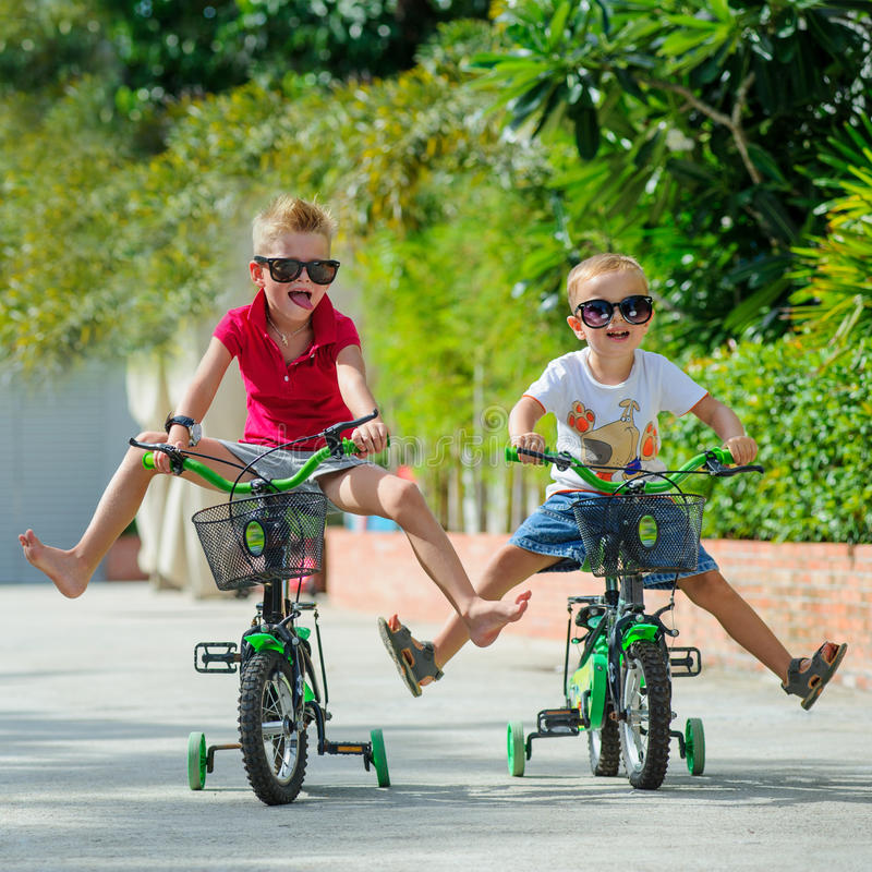 Two cute boys riding on bicycles, legs raised royalty free stock images