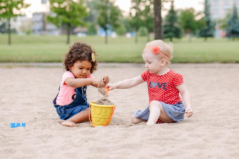 Two cute Caucasian and hispanic latin toddlers babies children sitting in sandbox playing with plastic colorful toys royalty free stock photos