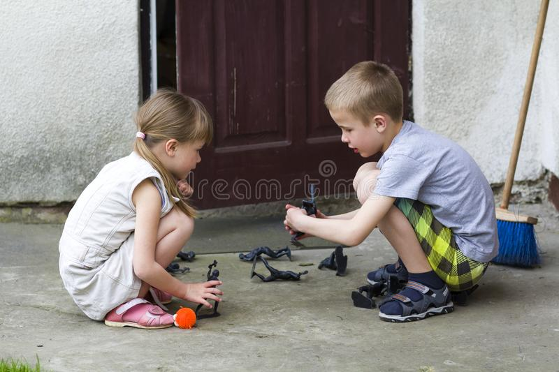 Two cute children blond pretty preschool girl and handsome boy playing outdoors with plastic toys on warm summer day on background stock photos