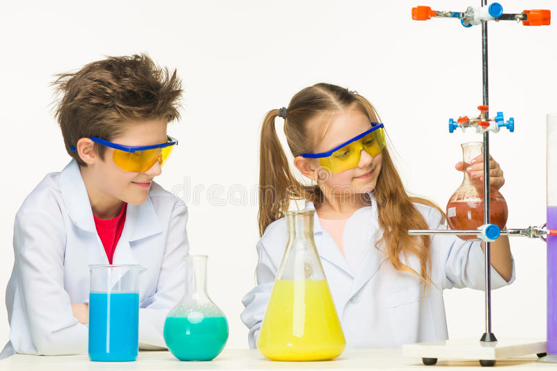 Two cute children at chemistry lesson making royalty free stock photos