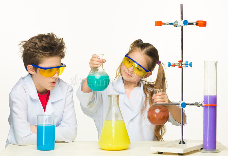 Two cute children at chemistry lesson making stock photos