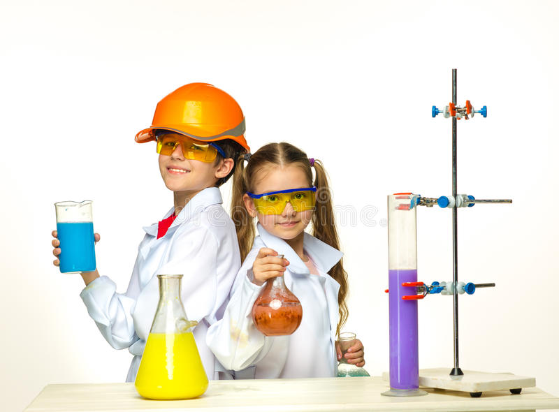 Two cute children at chemistry lesson making. Experiments on white background stock image