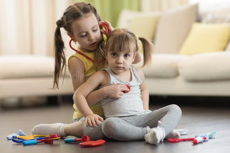 Two preschooler children, cute toddler girl and her older kid sister, playing doctor and hospital using stethoscope toy and other. Two cute children, cute stock photos