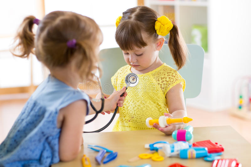Two cute children playing doctor and hospital using stethoscope. Friends girls having fun at home or preschool. stock image