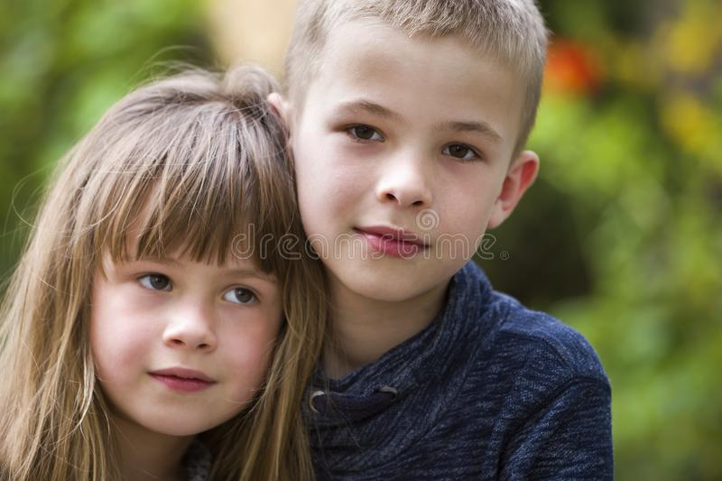 Two cute fair-haired children siblings, young boy brother and sister girl outdoors on bright sunny green bokeh background. Family stock image