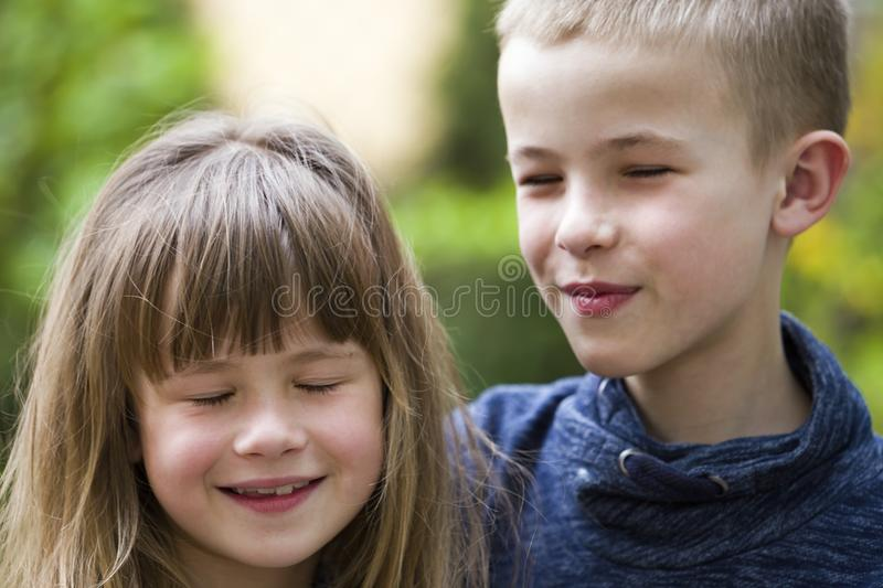 Two cute fair-haired children siblings, young boy brother and sister girl outdoors on bright sunny green bokeh background. Family stock photography