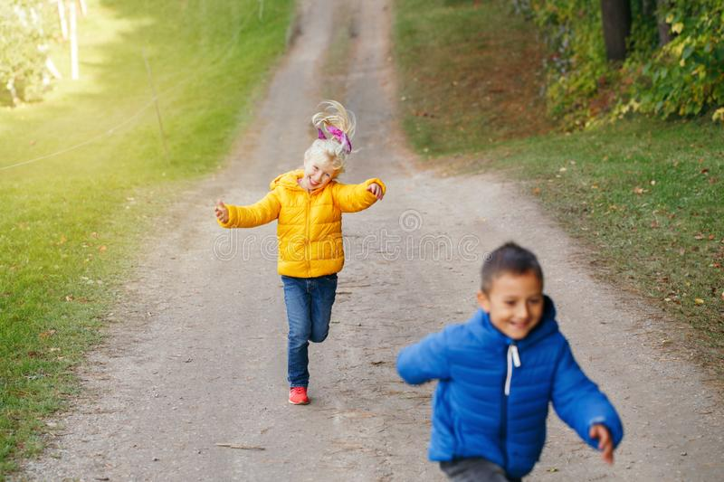 Two cute funny preschool Caucasian children boy girl running playing in park outside on autumn fall day. royalty free stock photography
