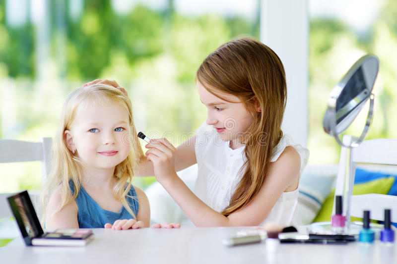 Two cute funny sisters applying make-up on sunny summer day at home stock image