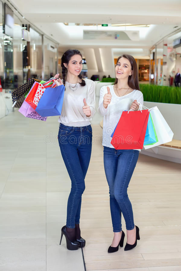 Two cute girl walks in the Mall with gift bags, showing thumbs-up. royalty free stock images