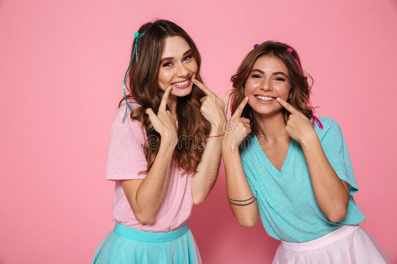Two cute girls dressed in colorful clothes touching with fingers. Those cheeks, looking at camera, isolated on pink background royalty free stock photo