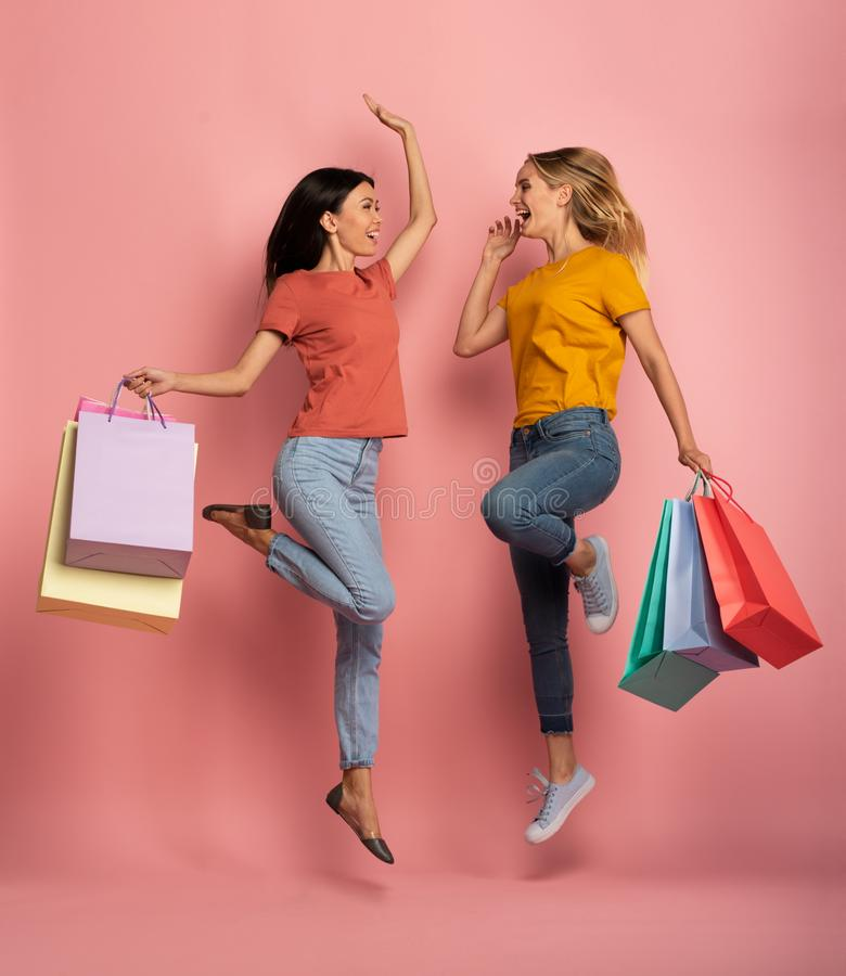 Two girls are happy after shopping. Joyful expression. Shop concept. Pink background stock image