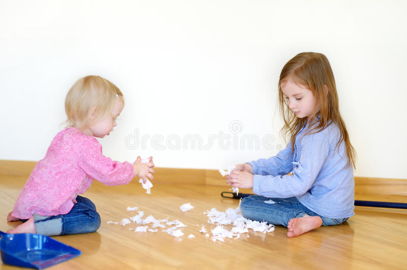 Two cute girls helping her mom to clean up stock photography