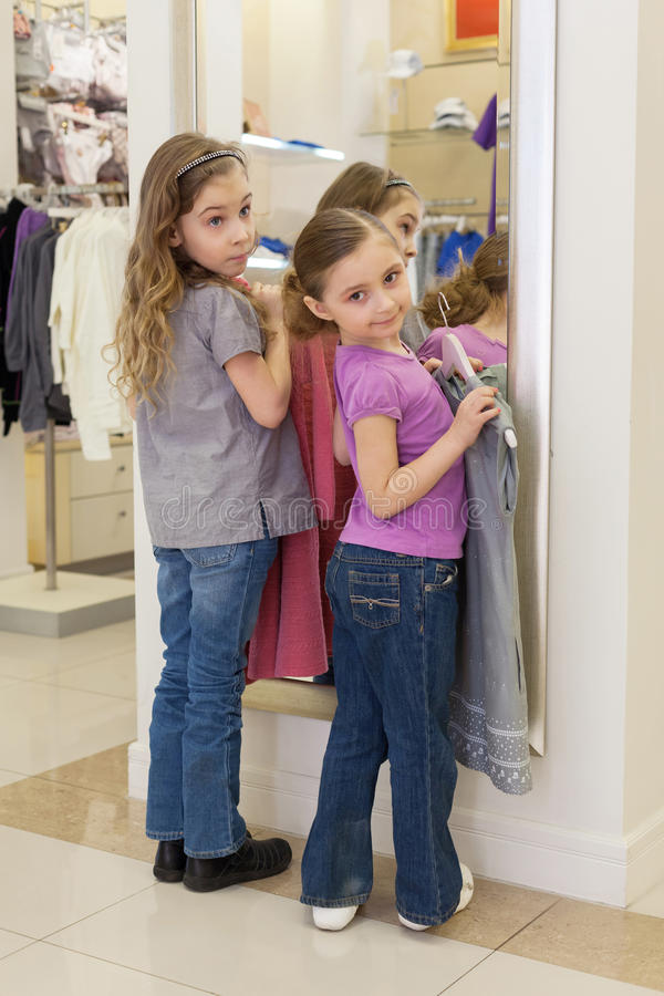 Two cute girls near a mirror try on clothes in a store for Mirror warehouse near me