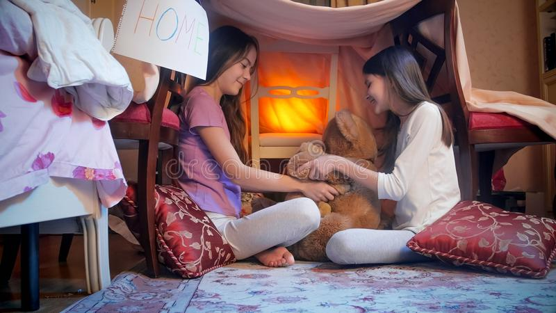 Two cute girls in pajamas playing with teddy bears in selfmade tent at night. Two girls in pajamas playing with teddy bears in selfmade tent at night royalty free stock image