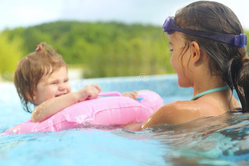 Two cute girls playing in swimming pool stock images