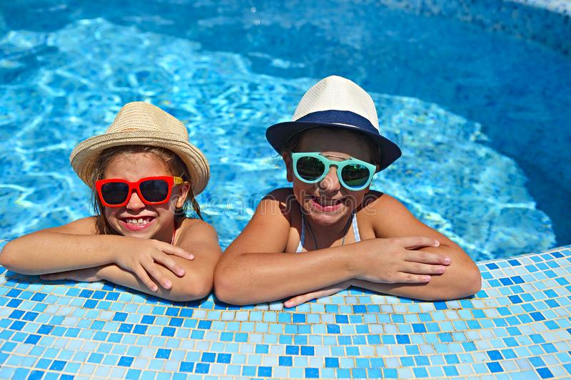 Two cute girls playing in swimming pool. Summer vacation and travel concept royalty free stock photos