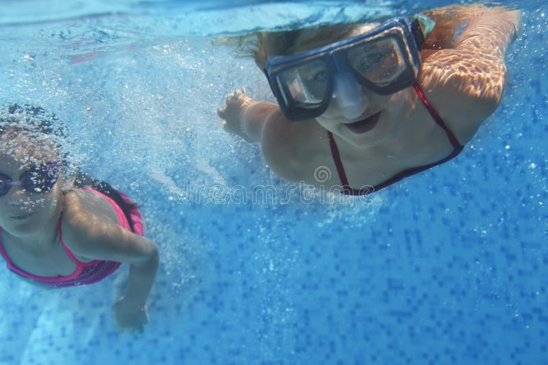 Two cute girls playing in swimming pool royalty free stock photo