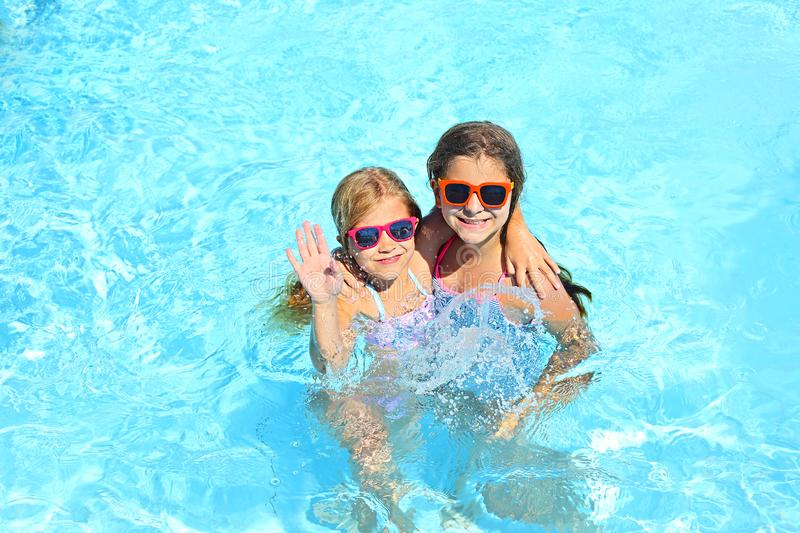 Two cute girls playing in swimming pool royalty free stock images