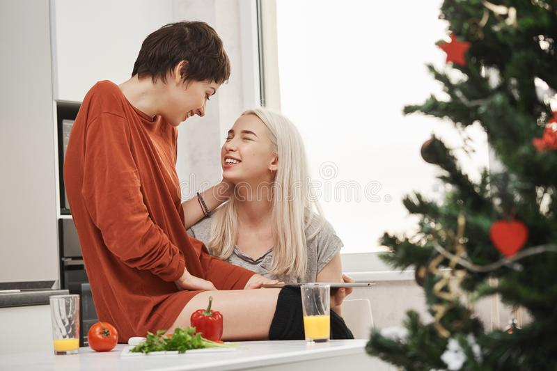 Two cute girls sitting in kitchen while talking and laughing during breakfast near christmas tree. Typical happy morning. Of tender girlfriends in relationship royalty free stock image
