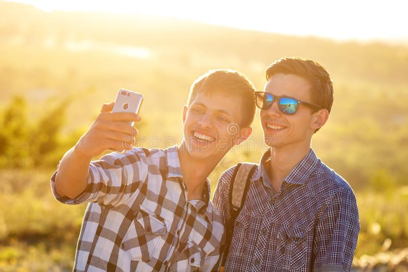 Two cute guys take selfies happy friends are photographed on the phone.  stock photos