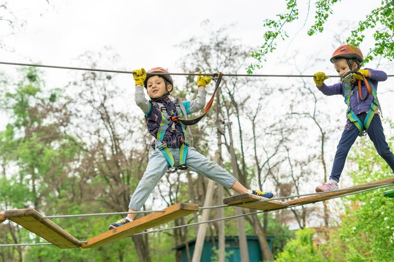 Two cute happy young children, boy and girl in protective harness, carbine and safety helmets on rope way on bright sunny day on. Green foliage bokeh background royalty free stock images