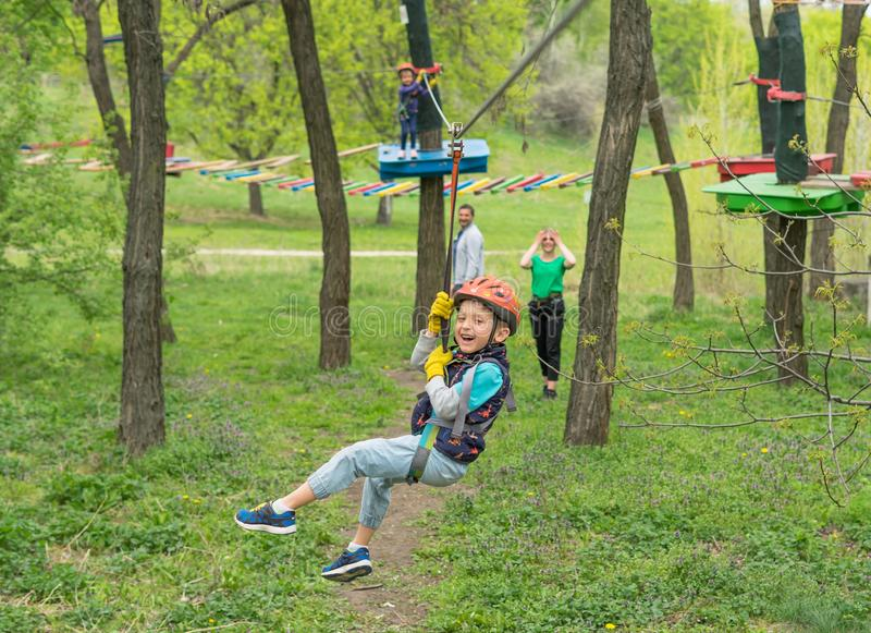 Two cute happy young children, boy and girl in protective harness, carbine and safety helmets on rope way on bright sunny day on. Green foliage bokeh background stock images