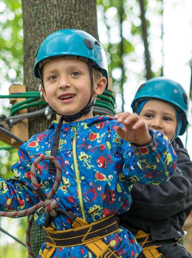 Two cute happy young children, boy and girl in protective harness, carbine and safety helmets on rope way on bright sunny day on. Green foliage bokeh background stock photo