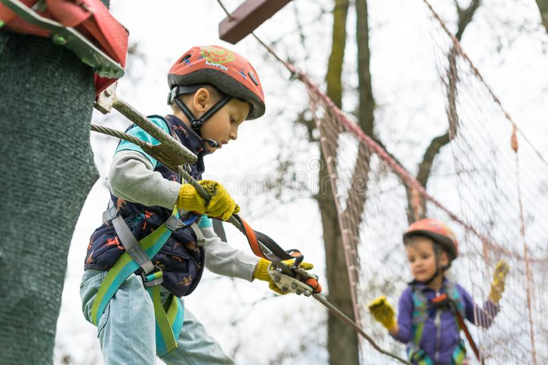 Two cute happy young children, boy and girl in protective harness, carbine and safety helmets on rope way on bright sunny day on. Green foliage bokeh background royalty free stock photos