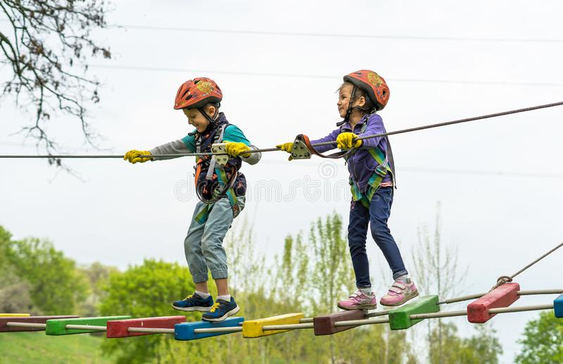 Two cute happy young children, boy and girl in protective harness, carbine and safety helmets on rope way on bright sunny day on. Green foliage bokeh background royalty free stock image