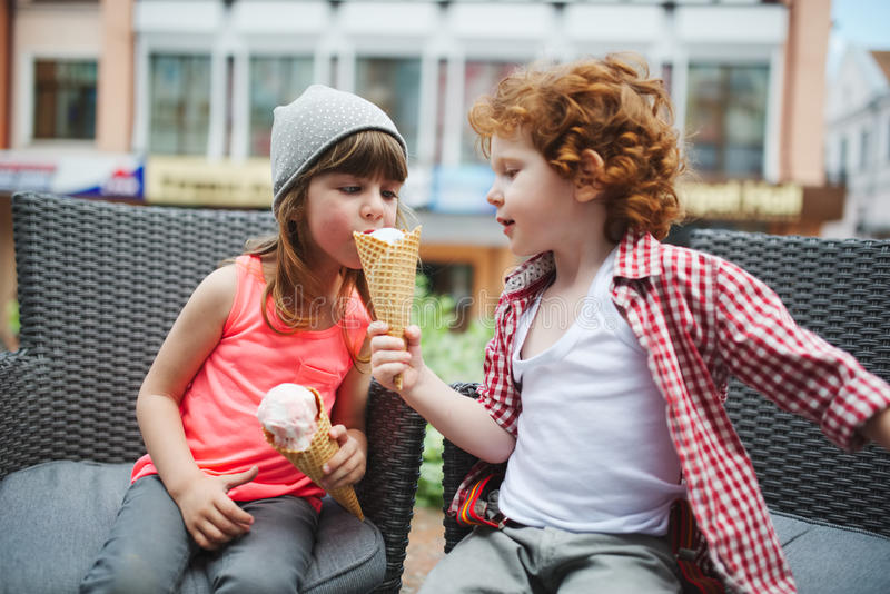 Two cute hipsters eating icecream stock photo