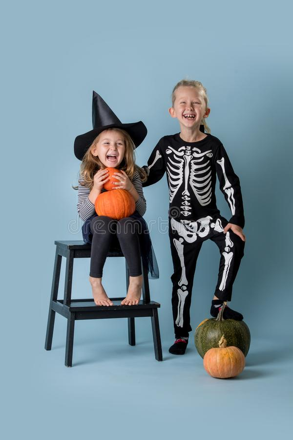 Two cute kids, boy and girl wearing witch and skeleton costumes over blue royalty free stock photos