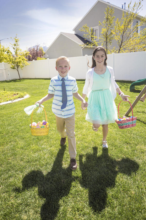 Two cute kids enjoying an Easter Egg Hunt Outdoors royalty free stock photo