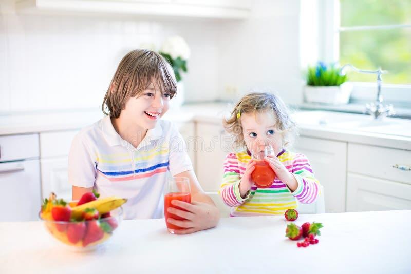 Two cute kids having fruit for breakfast drinking juice stock photography