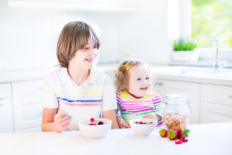 Two cute kids having fruit for breakfast drinking juice stock photo