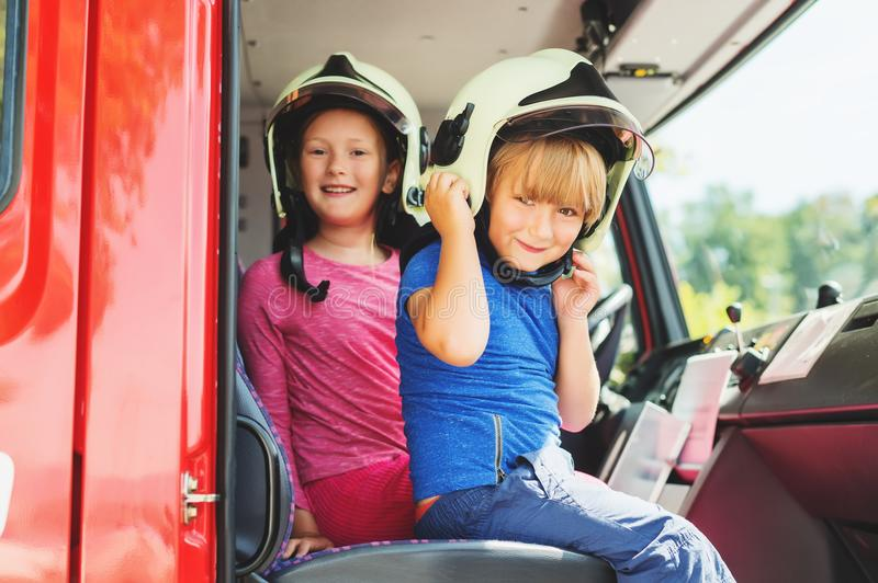 Two cute kids playing in fire truck. Pretending to be firefighters, open doors day at fire station. Future profession for children. Educational program for royalty free stock photography
