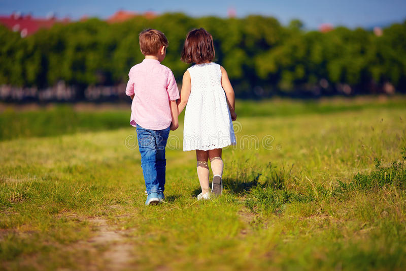 Two cute kids walking away on summer field royalty free stock image
