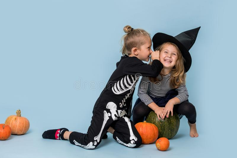 Two cute kids in witch and skeleton costumes gossiping over blue background royalty free stock photos