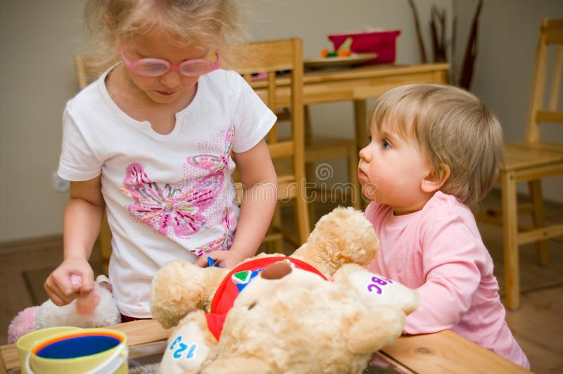 Two little girls playing together at home with plush toys stock images