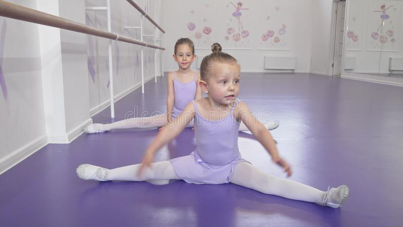 Two cute little ballerinas girls stretching at ballet class doing splits stock image