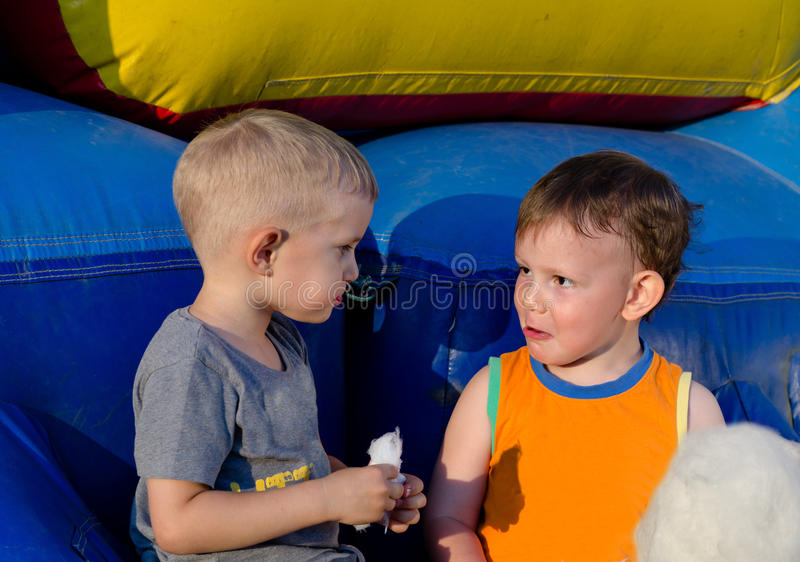 Two cute little boys enjoying cotton candy stock images