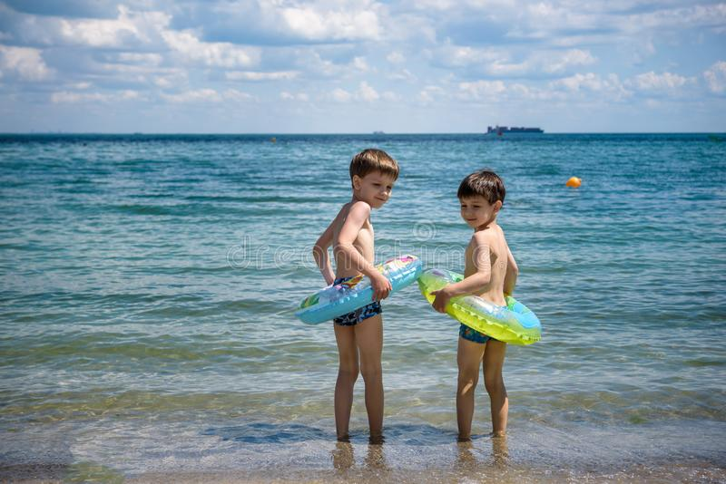 Two cute little brother boy stand on the beach in swimming trunks goes swimming with inflatable ring. Safe water activities with royalty free stock image