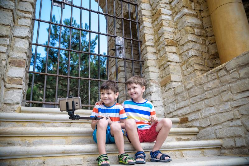 Two cute little brothers sitting on stairs in Italian town. Make selfie on mobile phone. Kids smiling and happy having leisure stock photo