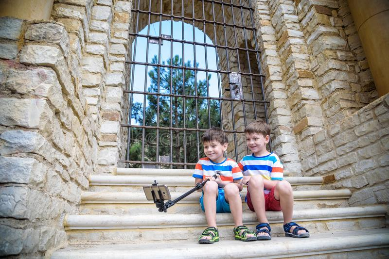 Two cute little brothers sitting on stairs in Italian town. Make selfie on mobile phone. Kids smiling and happy having leisure stock image