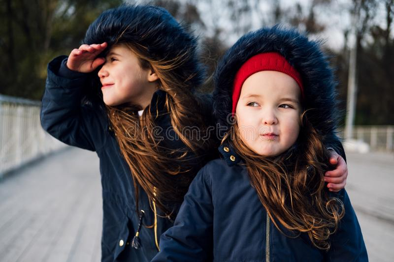 Two cute little children hugging in autumn park. Close up lifestyle fashion portrait of two beautiful caucasian girls outdoors, we royalty free stock photography