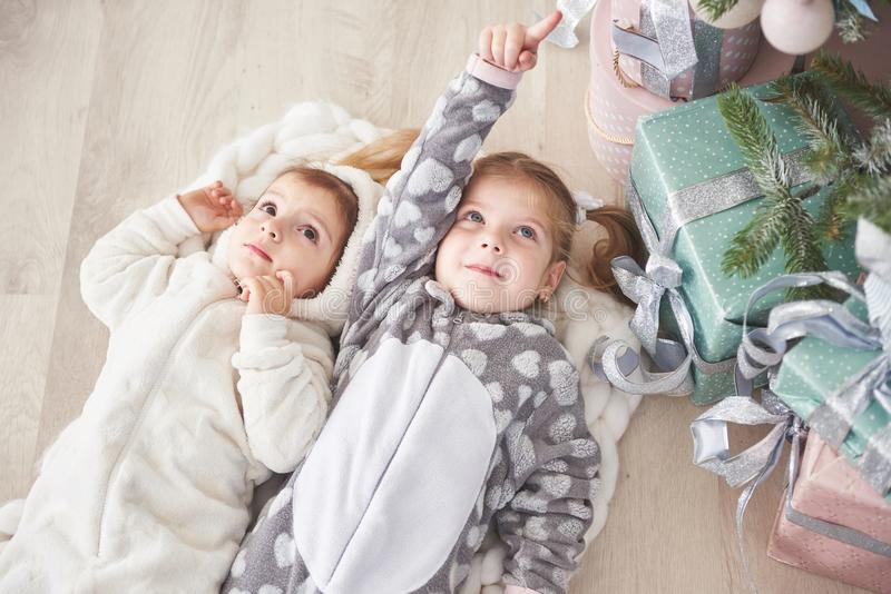 Two cute little girl in pajamas lying under Christmas tree among presents royalty free stock photos